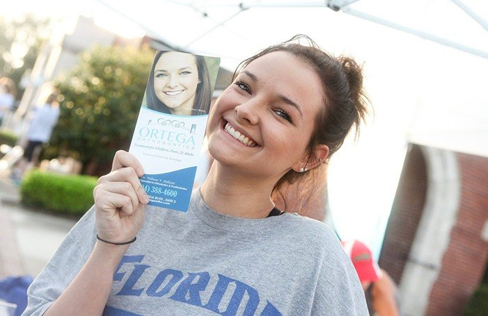 Woman smiling next to Ortega Orthodontics brochure with her picture