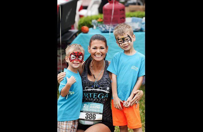 Team member and two kids at fun run