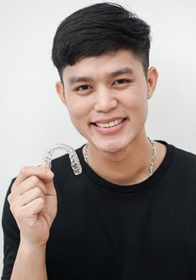 A young, male teen holding a clear aligner
