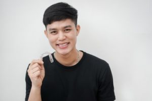 young man holding a clear aligner in Jacksonville